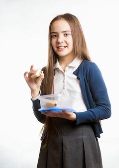 Portret ślicznej uśmiechniętej uczennicy trzymającej kanapkę na białym tle