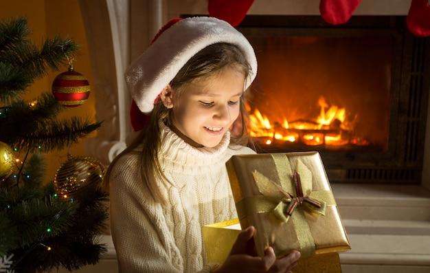 Portret ślicznej wesołej dziewczyny w santa hat patrząc wewnątrz świątecznego pudełka na prezent