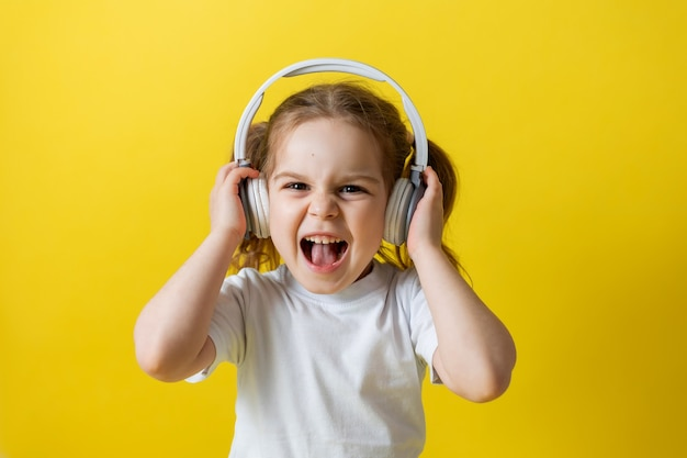 Portret ślicznej wesołej małej dziewczynki słuchającej muzyki z audiobookami z białymi słuchawkami