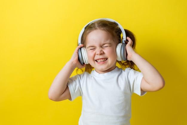 Portret ślicznej wesołej małej dziewczynki słuchającej muzyki z białymi słuchawkami koncepcja edukacji