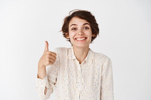 Portret ślicznej wspierającej dziewczyny pokazującej kciuki do góry i uśmiechający się dumnie, chwaląc cię, pokazując dobrze zrobiony, doskonały gest, stojąc zadowolony na białej ścianie