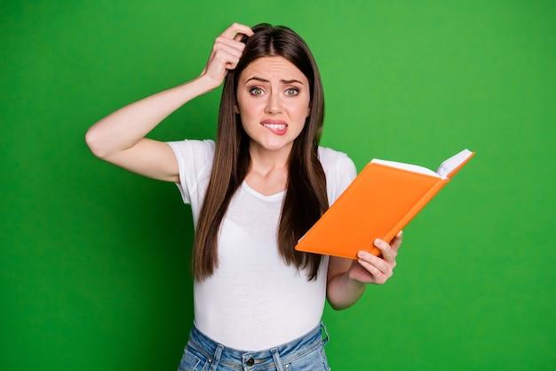 Portret ślicznej zdezorientowanej młodej kobiety trzymaj książkę, nie rozumiejąc, noś casual t-shirt na białym tle na zielonym tle