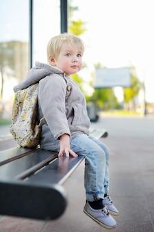 Portret śliczny berbeć chłopiec siedzi na ławce na autobusowej przerwie