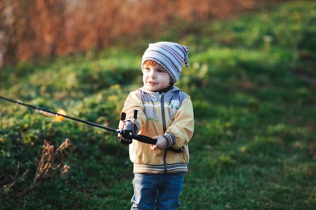 Portret śliczny chłopiec mienia połowu prącie