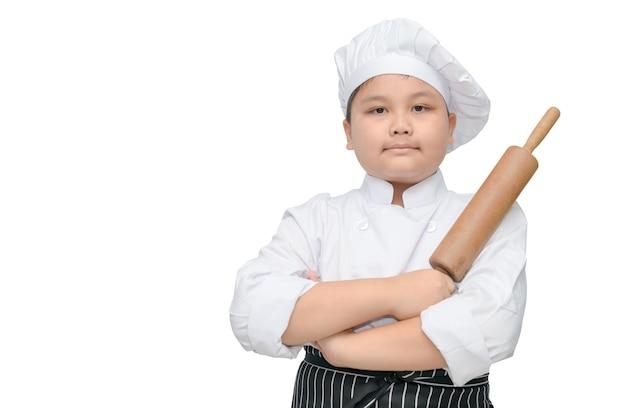 Portret śliczny chłopiec szef kuchni trzyma tocznej szpilki z kucbarskim kapeluszem i fartuchem odizolowywającymi na białym tle