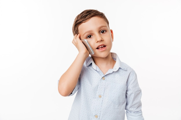 Portret śliczny małe dziecko opowiada na telefonie komórkowym