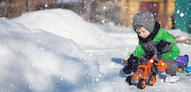 Portret śliczny maluch siedzi na śniegu i bawi się zabawką swojego żółtego ciągnika w parku. dziecko bawiące się na zewnątrz