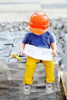 Portret śliczny mały budowniczy w hardhats czyta budowę rysuje outdoors