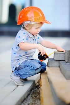 Portret śliczny mały budowniczy w hardhats z władcą pracuje outdoors