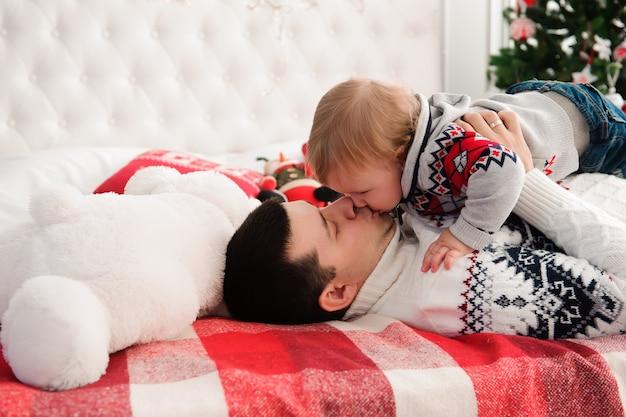Portret śliczny szczęśliwy ojciec i syn przy bożymi narodzeniami na łóżku.