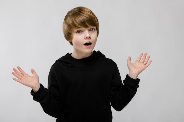 Portret śliczny zaskoczony mały chłopiec z otwartymi ustami i otwartymi ramionami