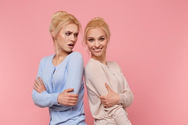 Portret ślicznych bliźniaczek blondynki, dziewczyna jest obrażona przez swoją siostrę, że pozuje lepiej od niej, wygląda na niezadowoloną, siostra uśmiecha się i patrzy w kamerę. dziewczyny stoi na różowym tle.