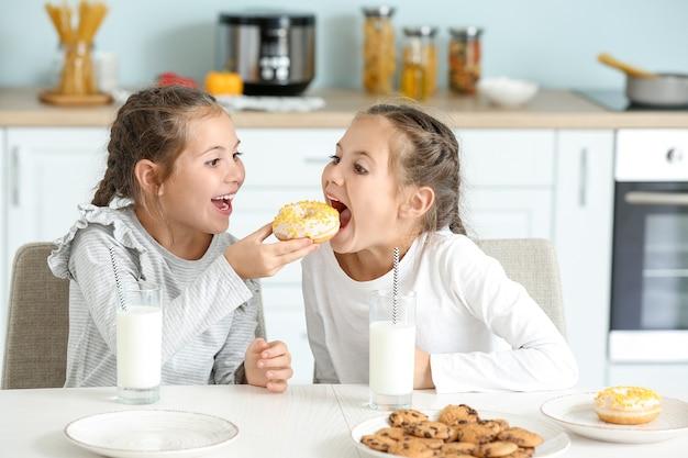 Portret ślicznych bliźniaczek jedzących pączki z mlekiem w kuchni