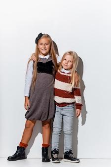 Portret ślicznych małych dziewczynek w stylowych dżinsach pozuje