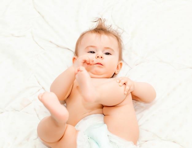 Portret słodkie dziecko 6 miesięcy leżąc na kocu. małe szczęśliwe dziecko
