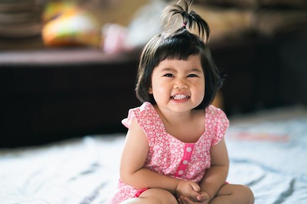 Portret słodkie dziecko siedzi na łóżku