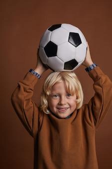 Portret słodkie dziecko z blond włosami trzymając piłkę nożną nad głową i patrząc na brązowym tle