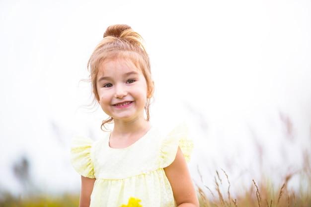 Portret słodkie dziewczyny w polu z dzikim kwiatem. dzieciństwo, wakacje na wsi, wolność i beztroska. czas letni. międzynarodowy dzień dziecka. odstraszacz komarów, rdzeń wiejski. skopiuj miejsce