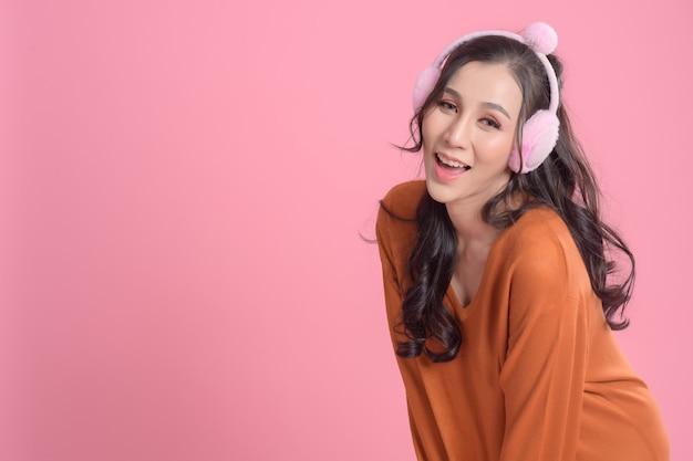 Portret słodkie kobiety ze słuchawkami na sobie pomarańczowy sweter na różowo.
