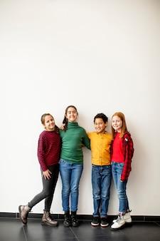 Portret słodkie małe dzieci w dżinsach patrząc na kamery i uśmiechnięte, stojąc przed białą ścianą