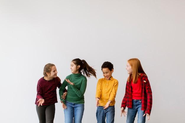 Portret słodkie małe dzieci w dżinsach, rozmawiając i uśmiechając się, chodząc na białej ścianie