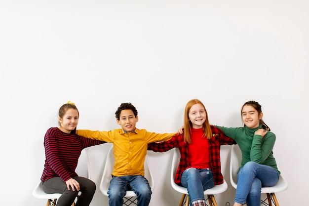 Portret słodkie małe dzieci w dżinsach siedzi na krzesłach pod białą ścianą