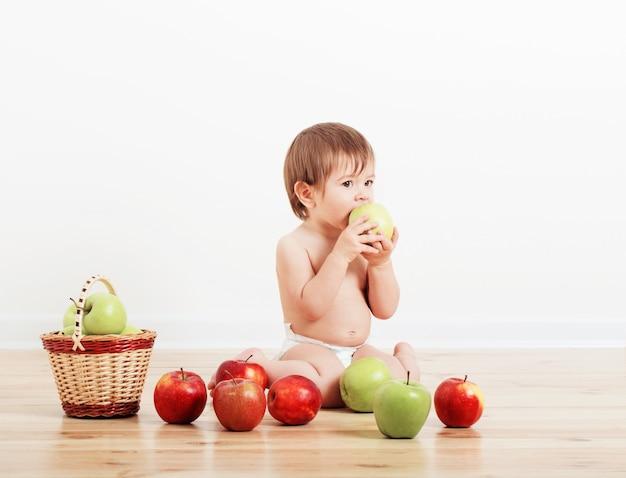 Portret słodkie małe dziecko z jabłkami w pomieszczeniach