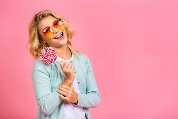 Portret słodkie młode małe dziecko dziewczynka jedzenie lizaka cukierki na białym tle nad różowym tle.