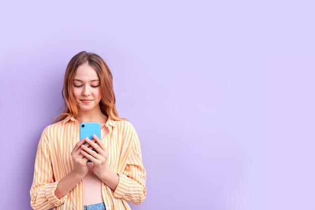 Portret słodkie nastolatka w koszuli na co dzień za pomocą telefonu komórkowego, czatowanie, pisanie wiadomości do kogoś, uśmiechanie się, na białym tle
