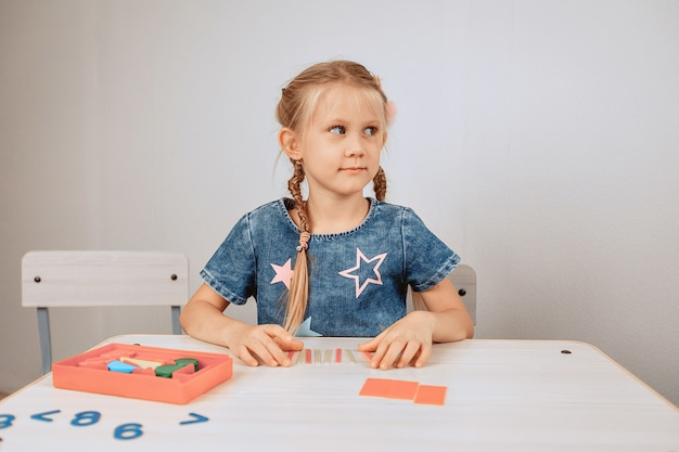 Portret słodkie słodkie dziecko siedzi przy białym stole i rozwiązuje intelektualne problemy i łamigłówki. rozwój dziecka. koncepcja umysłu. zdjęcie z hałasem