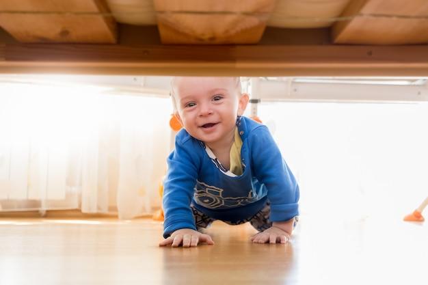 Portret słodkiego chłopca czołgającego się i patrzącego pod łóżko