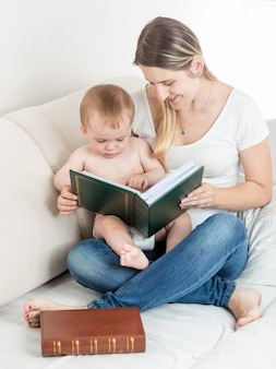 Portret słodkiego chłopca i matki patrząc na zdjęcia w rodzinnym albumie