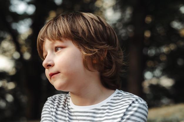 Portret słodkiego chłopca w lesie, w zamyśleniu patrząc z daleka, niebieskooka dziecko w szkole, dzień marzy w