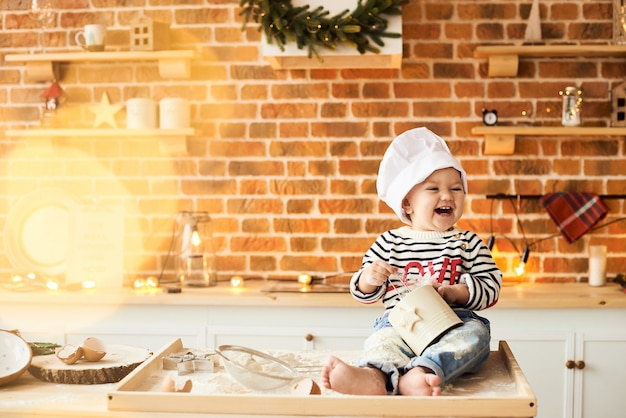 Portret słodkiego dzieciaka gotowanego i bawiącego się z mąką i ciastem w kuchni