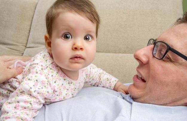 Portret słodkiego dziecka bawiącego się ze swoim szczęśliwym ojcem leżącym nad jego brzuchem na kanapie w domu