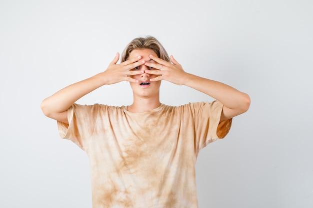 Portret słodkiego nastoletniego chłopca zerkającego przez palce w koszulce i patrzącego na zdziwiony widok z przodu