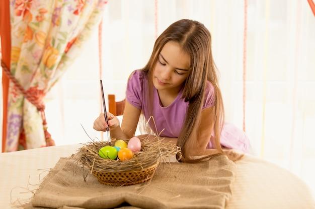 Portret słodkiej dziewczyny dekorującej pisanki w koszyku