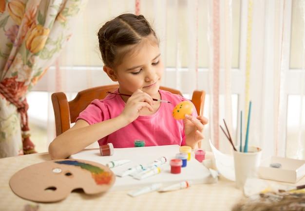 Portret słodkiej dziewczyny malującej jajko wielkanocne w domu