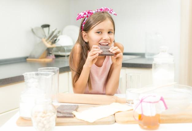 Portret słodkiej dziewczyny opierając się na stole w kuchni i jedząc czekoladę