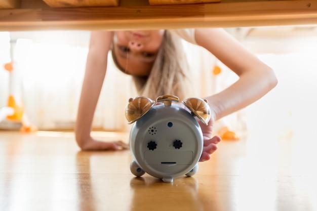 Portret słodkiej dziewczyny sięgającej po budzik pod łóżkiem