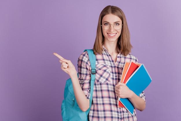 Portret słodkiej młodej dziewczyny studentki trzymającej notatnik torba punkt palec pusta przestrzeń porady izolowane na fioletowym tle