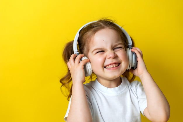 Portret słodkiej wesołej dziewczynki słuchającej muzyki z białymi słuchawkami na żółtym tle