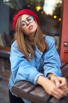 Portret słoneczny słoneczny styl życia moda młoda kobieta stylowa hipster spaceru na ulicy, ubrany w ładny modny strój z czerwonym kapeluszem