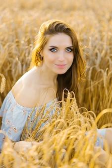 Portret słowiańskiej dziewczyny z rudymi włosami siedzi w polu pszenicy