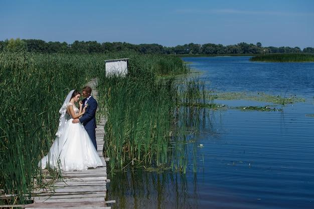 Portret ślub para spaceru na drewniany most w pobliżu jeziora. szczęśliwa panna młoda i pan młody delikatnie przytula na zewnątrz. młoda para zakochanych raduje się sobą w naturze w pobliżu rzeki.