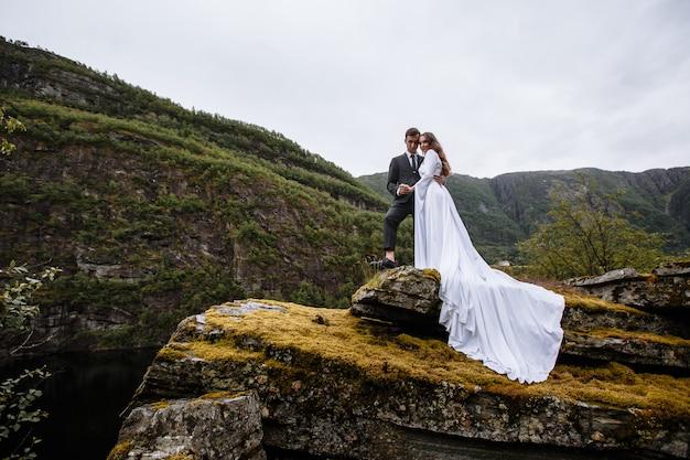 Portret ślubna pary pozycja na skale. nowożeńcy tulą się do siebie
