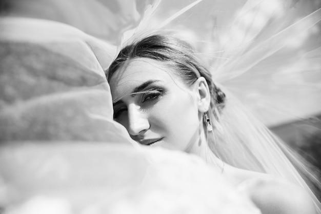 Portret ślubny panny młodej kobiety pod białym welonem. dziewczyna w sukni ślubnej z bukietem kwiatów w dłoniach