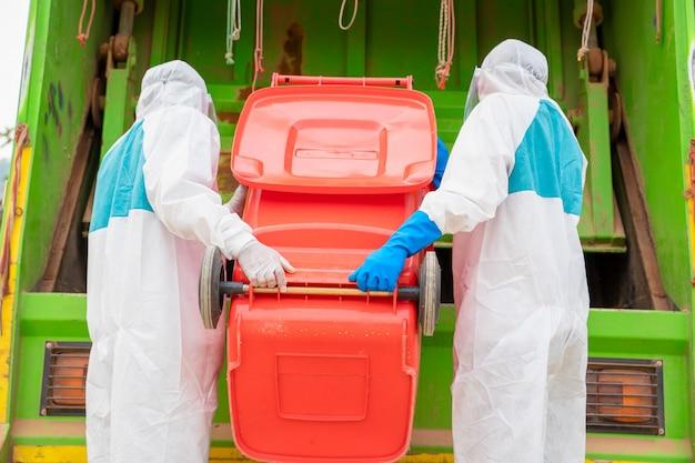 Portret śmieciarza w odzieży ochronnej ppe firmy hazmat nosić gumę medyczną z ciężarówką ładującą śmieci i kosz na śmieci, choroba coronavirus 2019, coronavirus zmienił się w globalny kryzys.