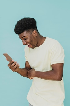 Portret śmiejącego się mężczyzny patrząc na smartfona