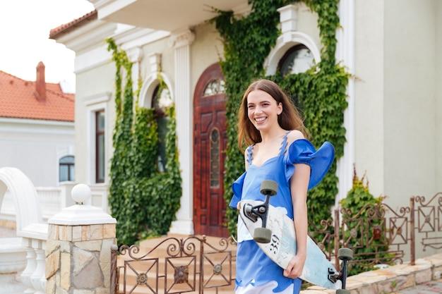 Portret śmiejącej się kobiety łyżwiarz spaceru i odwracając na zewnątrz